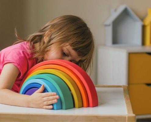 Cet enfant joue avec un arc-en-ciel en bois